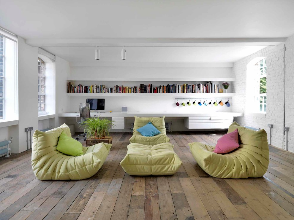 Living room library - industrial open concept medium tone wood floor living room library idea in London with white walls