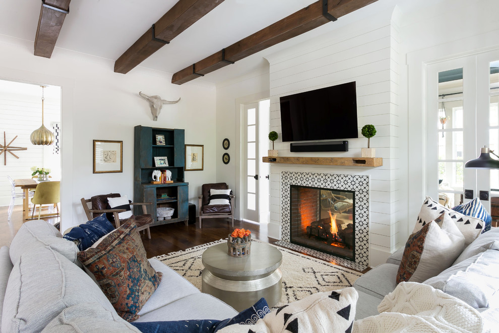 Living room - coastal dark wood floor and brown floor living room idea in Charleston with white walls, a two-sided fireplace, a tile fireplace and a wall-mounted tv