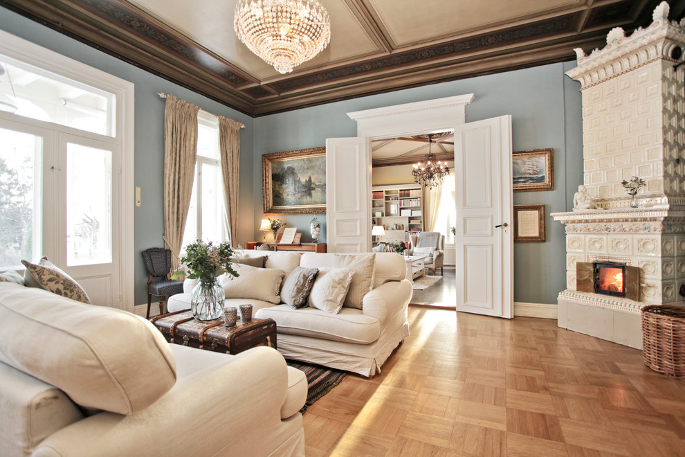 Elegant medium tone wood floor living room photo in Other with blue walls and a corner fireplace