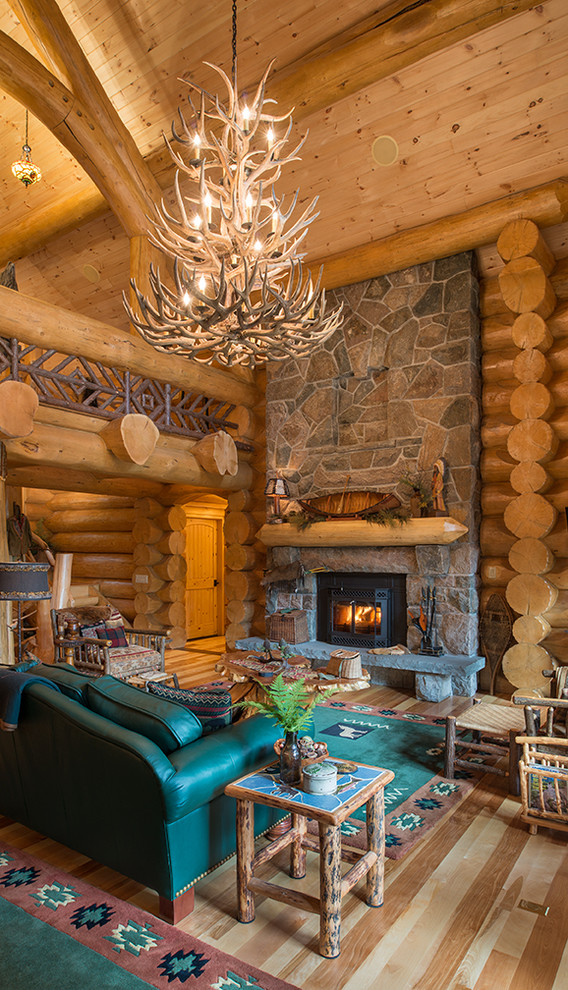 Example of a mountain style medium tone wood floor living room design in New York with a standard fireplace and a stone fireplace