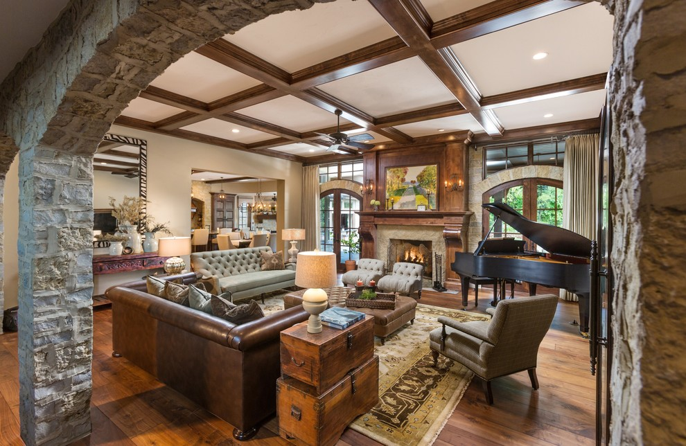 Example of a large classic open concept medium tone wood floor living room design in Milwaukee with a music area, beige walls, a standard fireplace, a stone fireplace and a wall-mounted tv