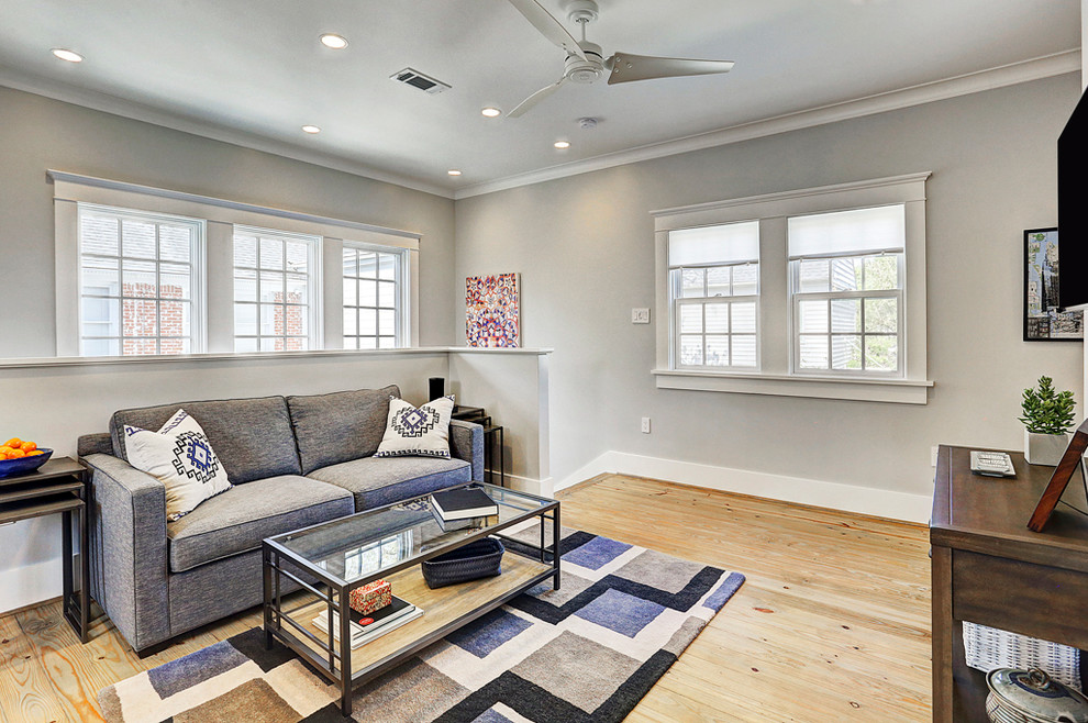 Inspiration for a mid-sized transitional open concept light wood floor and brown floor living room remodel in Houston with gray walls, no fireplace and a wall-mounted tv