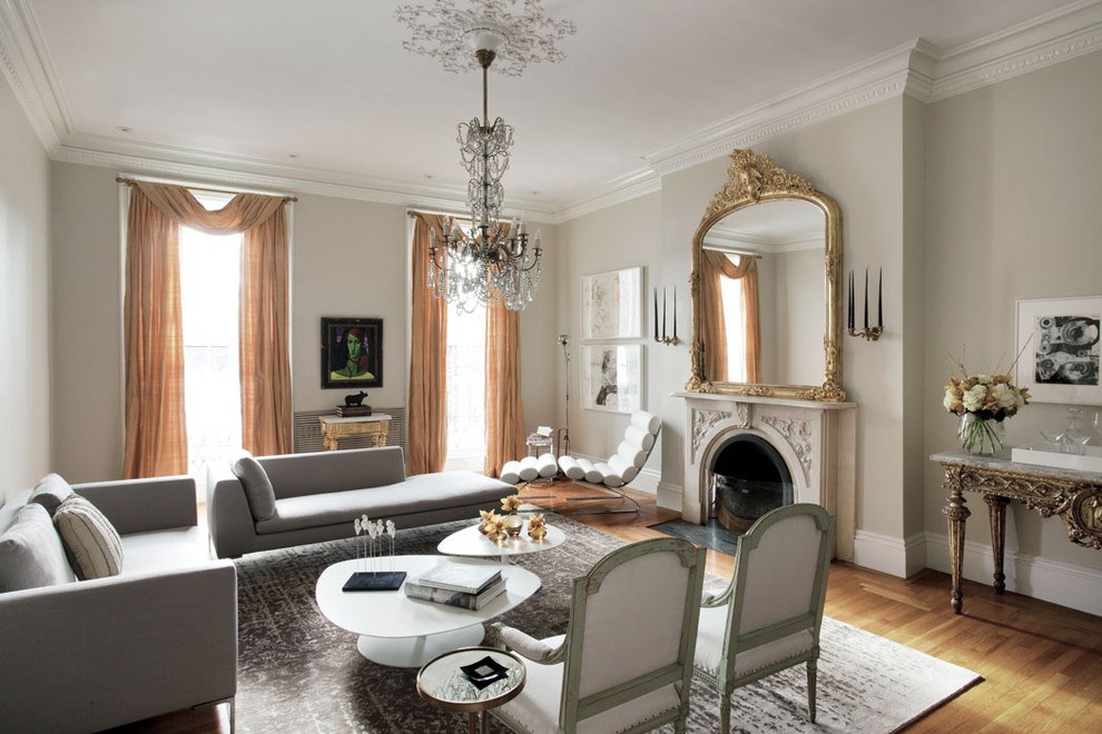 Example of a large eclectic medium tone wood floor living room design in Boston with beige walls, a standard fireplace, no tv and a stone fireplace