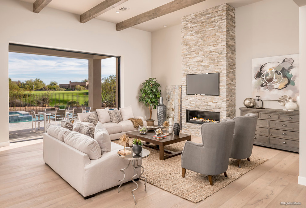 Large trendy open concept light wood floor living room photo in Phoenix with beige walls and a stone fireplace