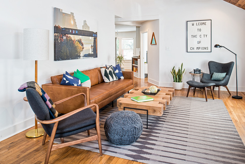 Inspiration for a mid-century modern medium tone wood floor living room remodel in Austin with white walls