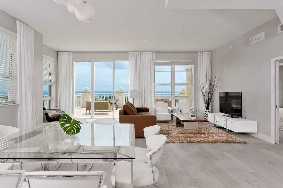 Inspiration for a contemporary open concept light wood floor and gray floor living room remodel in Miami with gray walls, no fireplace and a tv stand