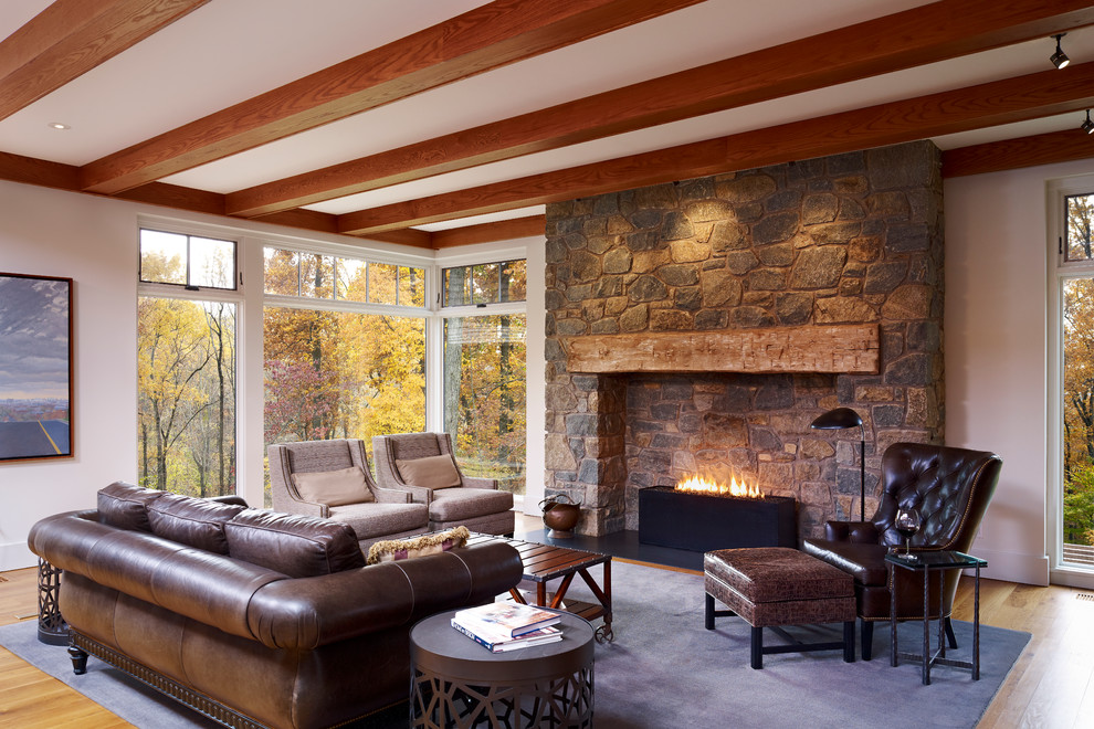 Example of a large country medium tone wood floor living room design in Philadelphia with a stone fireplace and a standard fireplace