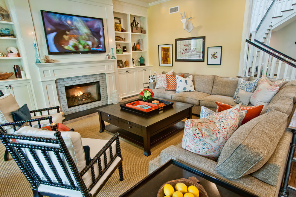 Example of a trendy living room design in Los Angeles with yellow walls, a standard fireplace and a brick fireplace