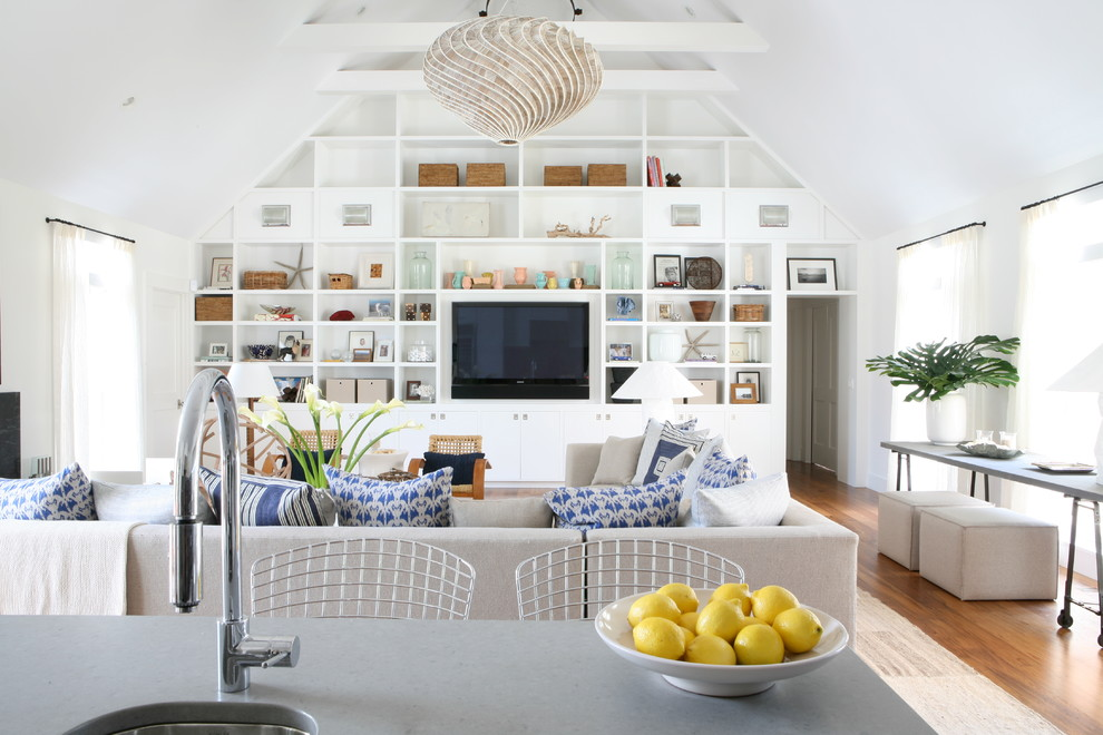 Example of a coastal open concept medium tone wood floor living room design in New York with white walls and a wall-mounted tv