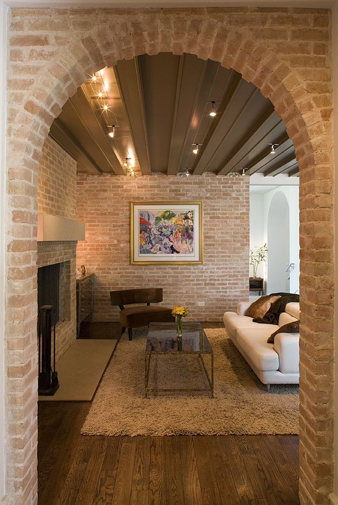 Inspiration for a rustic living room remodel in Austin with a brick fireplace