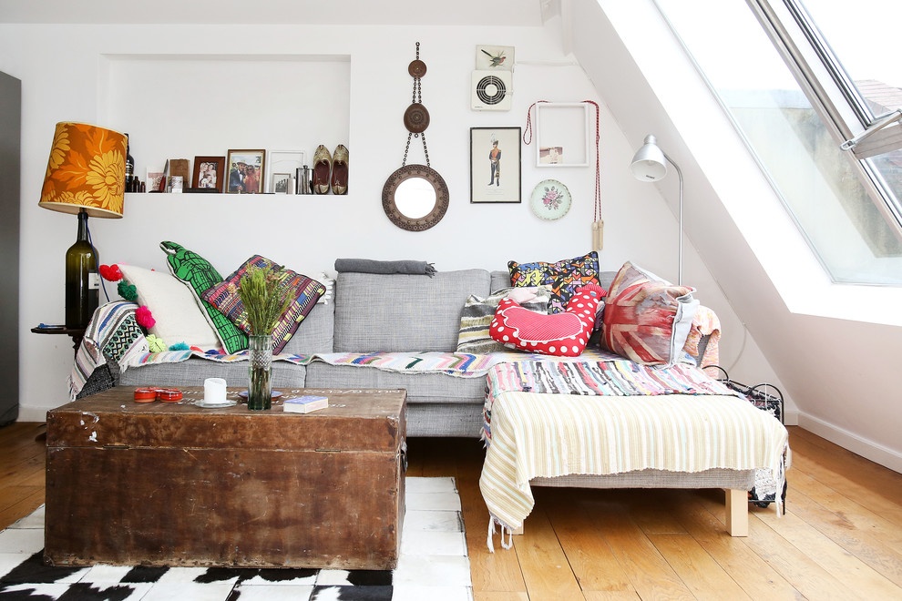 Example of an eclectic light wood floor living room design in London with white walls