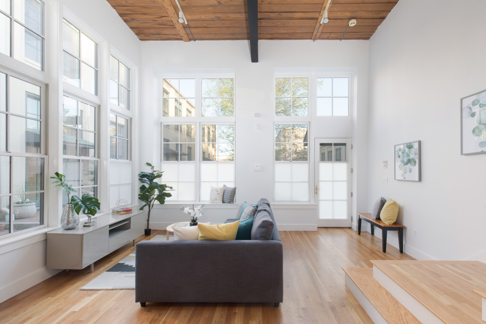 Inspiration for a large scandinavian open concept medium tone wood floor and beige floor living room remodel in Boston with white walls and no tv