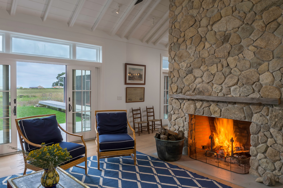 Example of a farmhouse open concept living room design in Boston with white walls, a standard fireplace and a stone fireplace