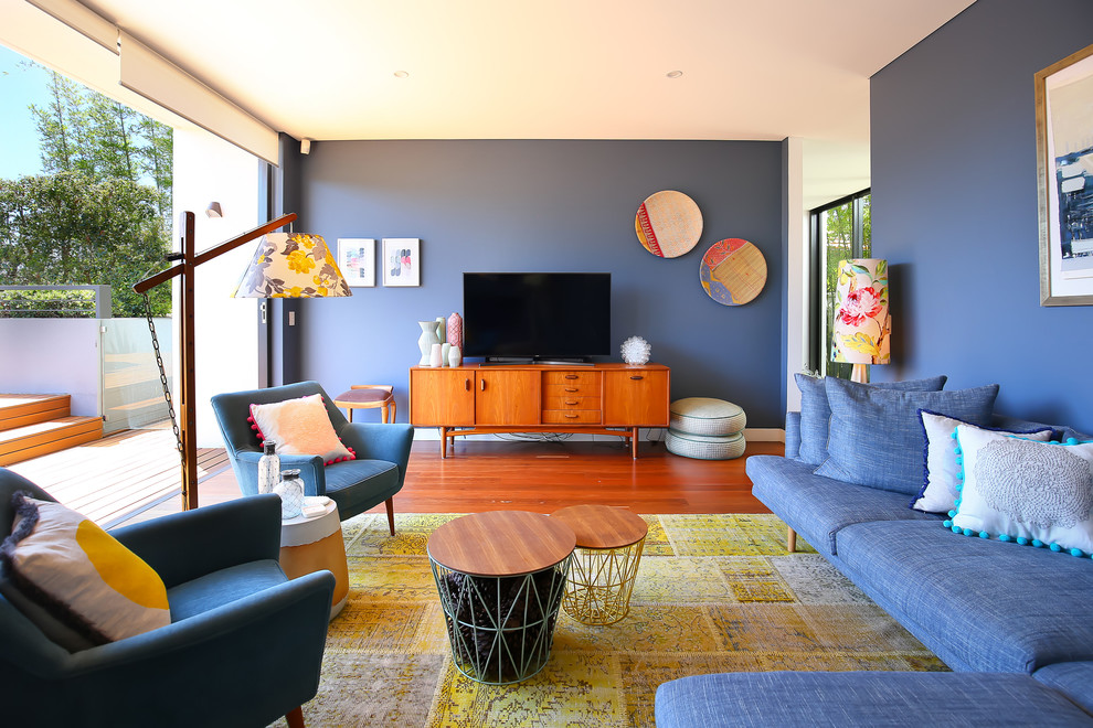 Mid-century modern enclosed medium tone wood floor living room photo in Sydney with blue walls and a tv stand