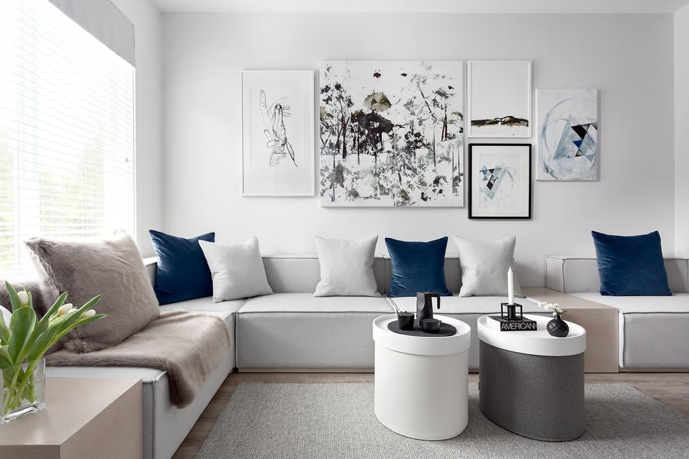 Living room - scandinavian medium tone wood floor living room idea in Vancouver with white walls