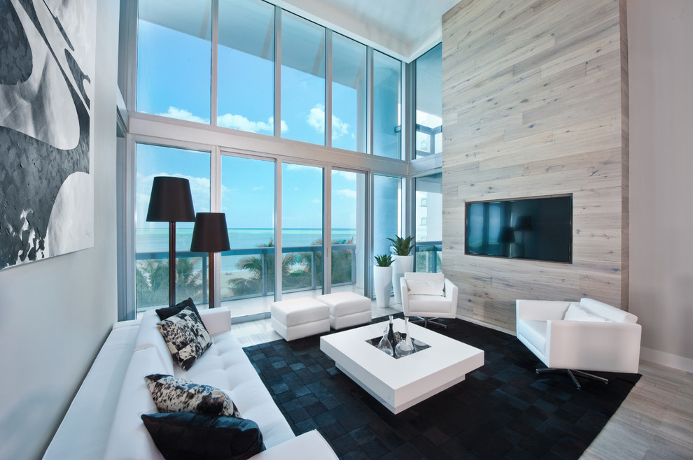 Example of a trendy living room design in Miami with gray walls and a wall-mounted tv