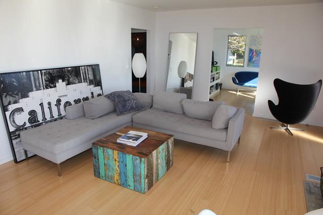Modelo de salón para visitas cerrado, minimalista, de tamaño medio, con paredes blancas, suelo de bambú, televisor colgado en la pared y suelo marrón