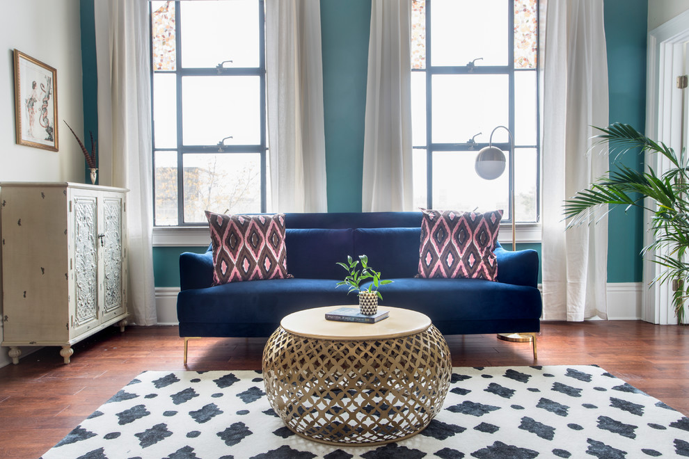 Example of a transitional medium tone wood floor and brown floor living room design in New Orleans with blue walls
