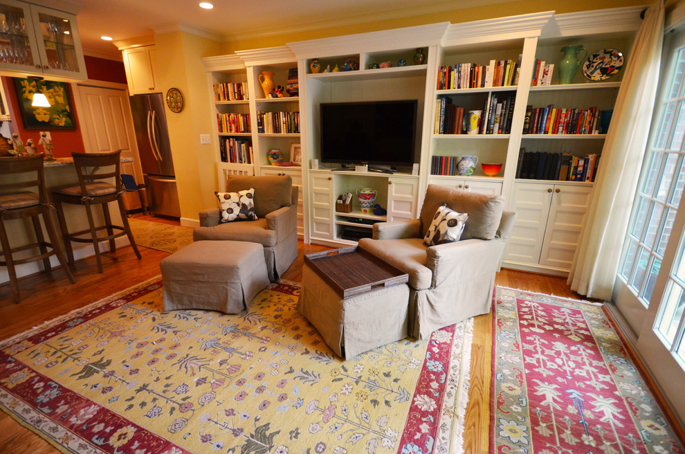 Mid-sized elegant open concept medium tone wood floor and brown floor living room library photo in DC Metro with yellow walls, no fireplace and a tv stand