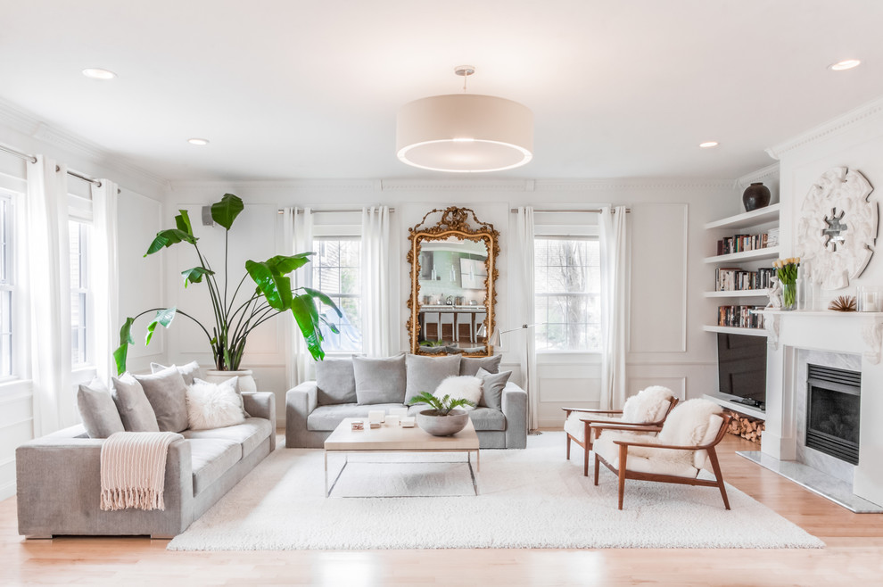 Example of a transitional formal light wood floor living room design in Boston with white walls and a standard fireplace