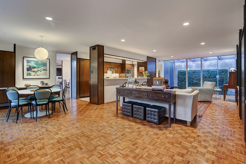 Example of a large mid-century modern open concept medium tone wood floor and brown floor living room design in Houston with white walls, no fireplace, a media wall and a music area