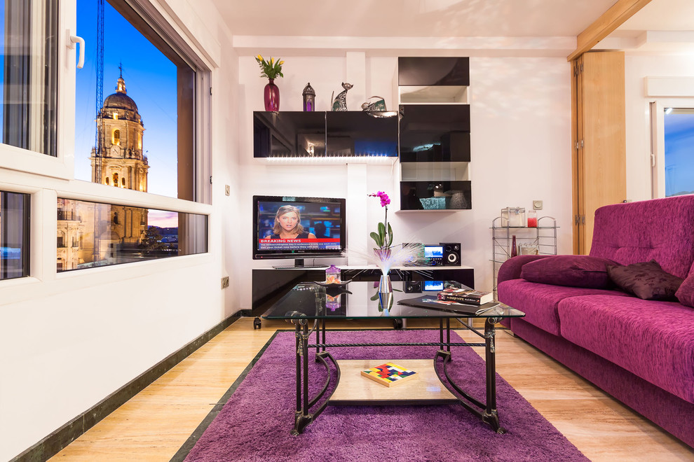 Small transitional light wood floor living room photo in Malaga with white walls and a tv stand