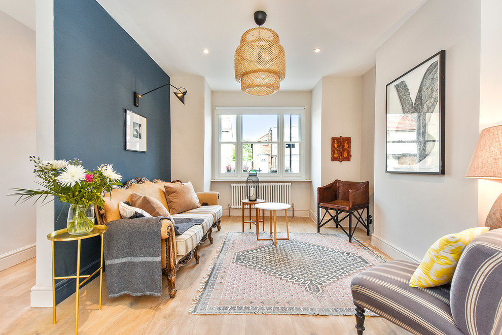 Mid-sized eclectic light wood floor living room photo in London with blue walls
