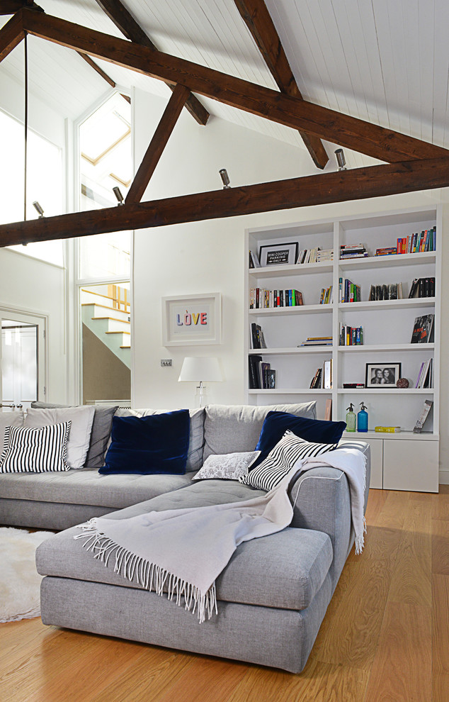 Trendy formal and open concept light wood floor living room photo in London with white walls