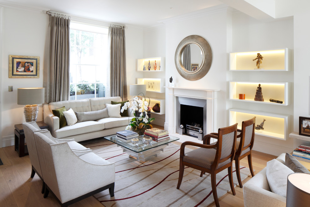 Transitional formal light wood floor living room photo in London with white walls, a standard fireplace and a metal fireplace