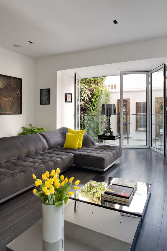 Inspiration for a large contemporary formal and enclosed dark wood floor and brown floor living room remodel in London with white walls, a standard fireplace, a plaster fireplace and a wall-mounted tv