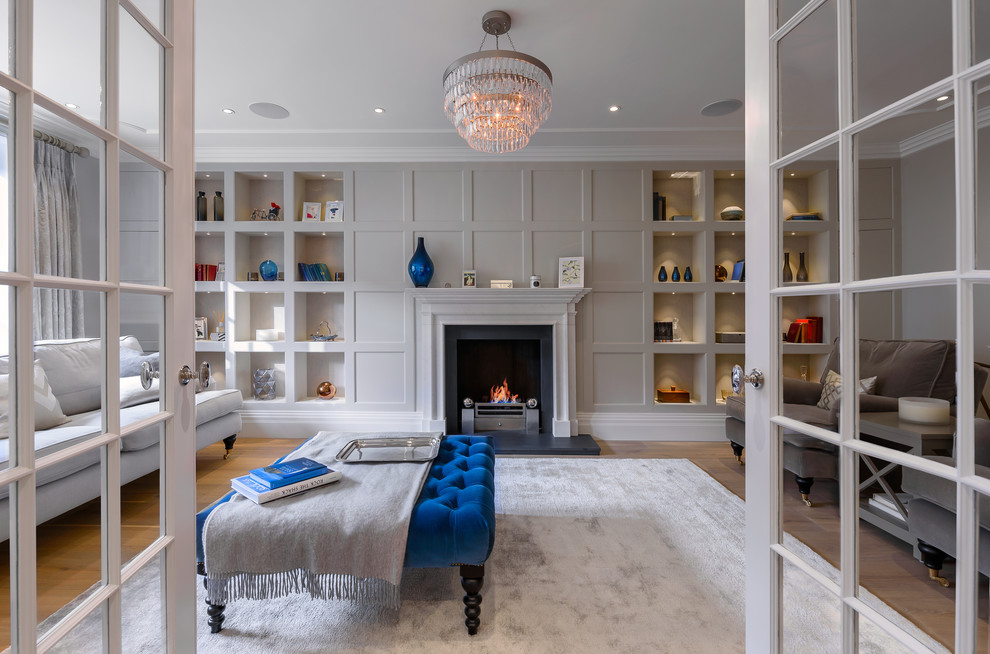 Large transitional formal and enclosed medium tone wood floor and brown floor living room photo in London with gray walls, no tv and a standard fireplace