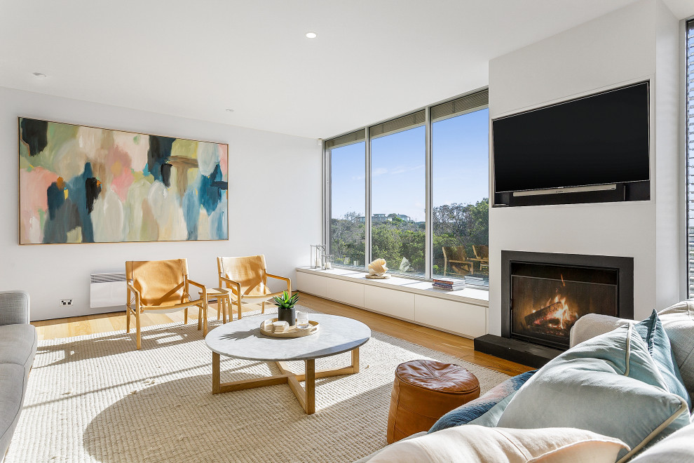 Example of a trendy open concept medium tone wood floor and brown floor living room design in Melbourne with white walls, a standard fireplace and a wall-mounted tv