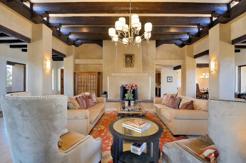 Living room - southwestern open concept beige floor living room idea in Albuquerque with beige walls, a standard fireplace, a plaster fireplace and no tv