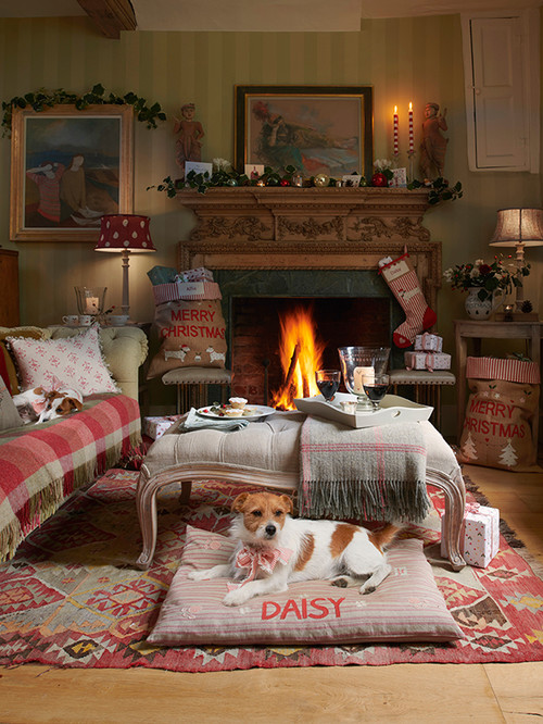 Holiday Decor Ideas for Dog Lovers - English christmas scene.  Living room decorated in rosy plaids with firs place and socking.  Dog in foreground lying on pillow type pink dog bed.