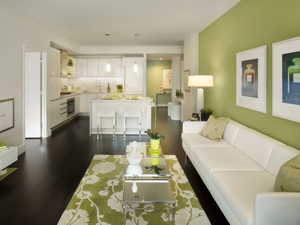 Example of a trendy open concept dark wood floor and black floor living room design in New York with green walls