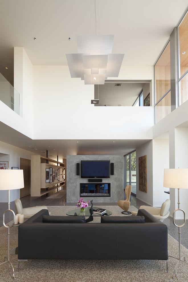 Large trendy open concept concrete floor living room photo in Austin with a wall-mounted tv, white walls, a two-sided fireplace and a concrete fireplace