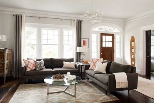 A living room with two gray couches sitting perpendicular to one another with a round glass top coffee table in the middle