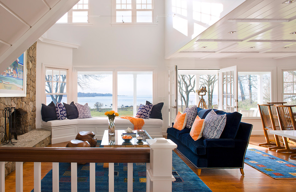 Example of a beach style open concept medium tone wood floor living room design in Bridgeport with white walls, a standard fireplace, a stone fireplace and no tv