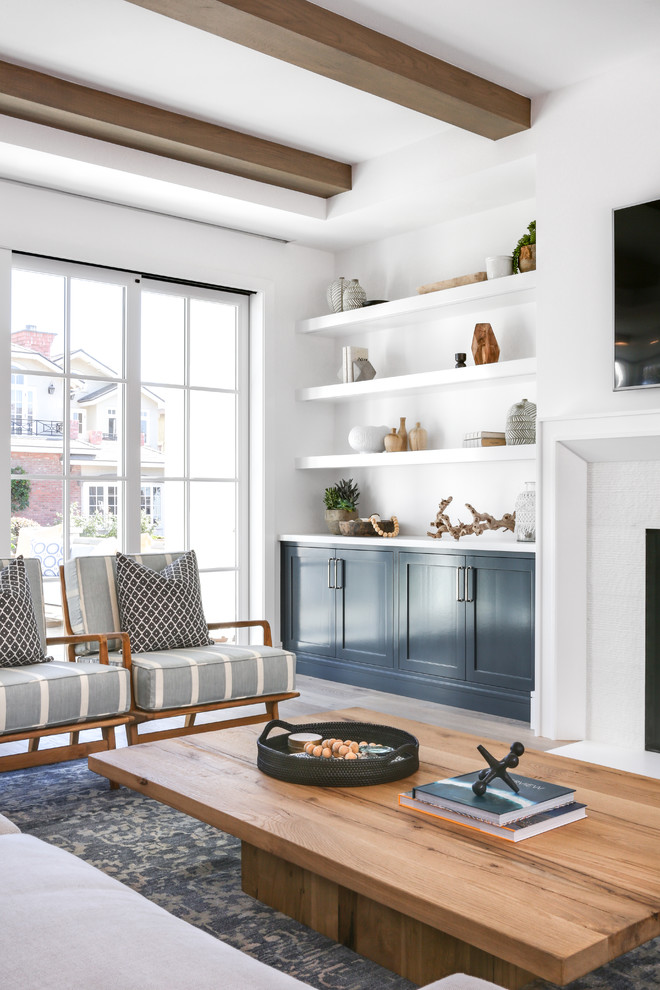 Large minimalist open concept medium tone wood floor and brown floor living room photo in Orange County with white walls, a standard fireplace, a tile fireplace and a wall-mounted tv