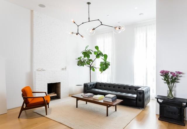 Foto di un soggiorno scandinavo aperto con pareti bianche, parquet chiaro, camino classico, cornice del camino in mattoni e nessuna TV