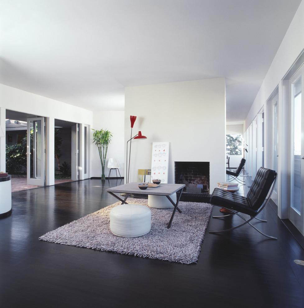Minimalist black floor living room photo in San Francisco with white walls