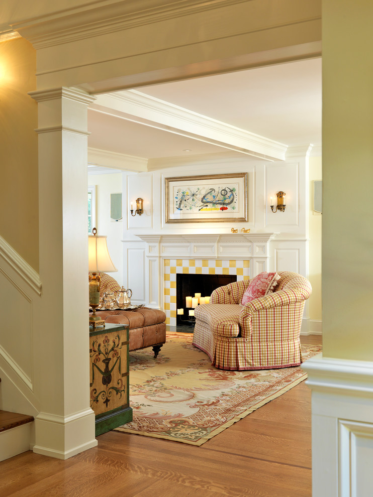 Elegant medium tone wood floor living room photo in Boston with a standard fireplace and a tile fireplace