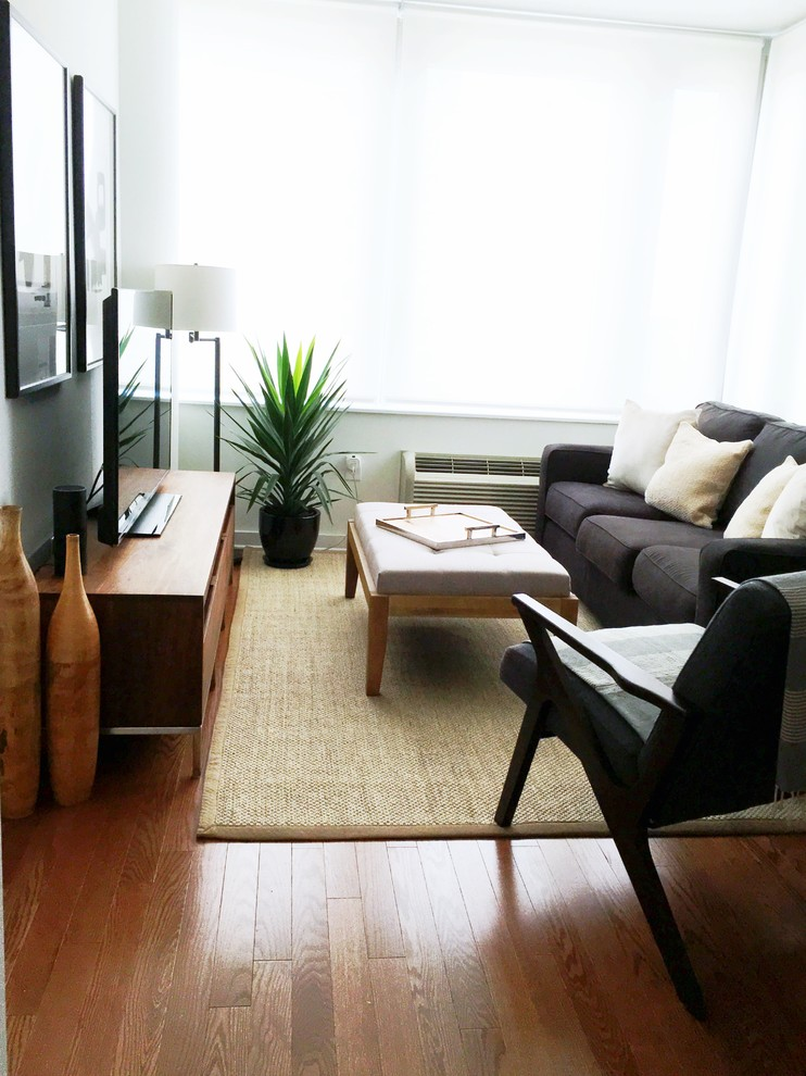 Living room - small modern formal and open concept medium tone wood floor and brown floor living room idea in New York with white walls, no fireplace and no tv