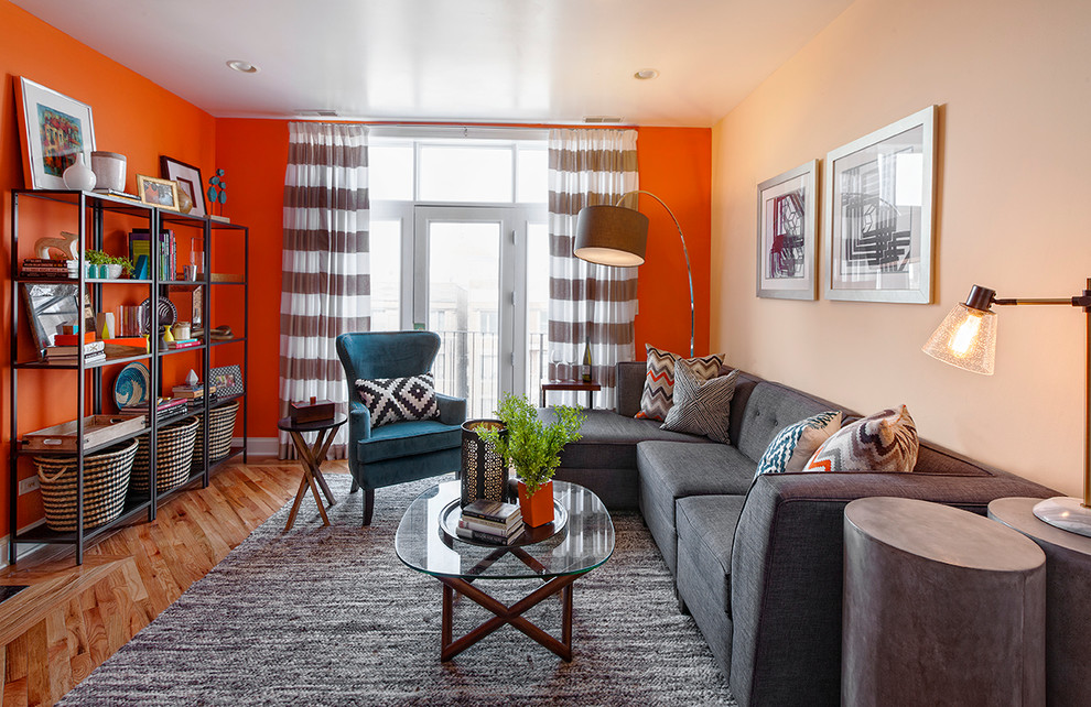 Inspiration for a small contemporary open concept light wood floor living room remodel in Chicago with orange walls and no fireplace