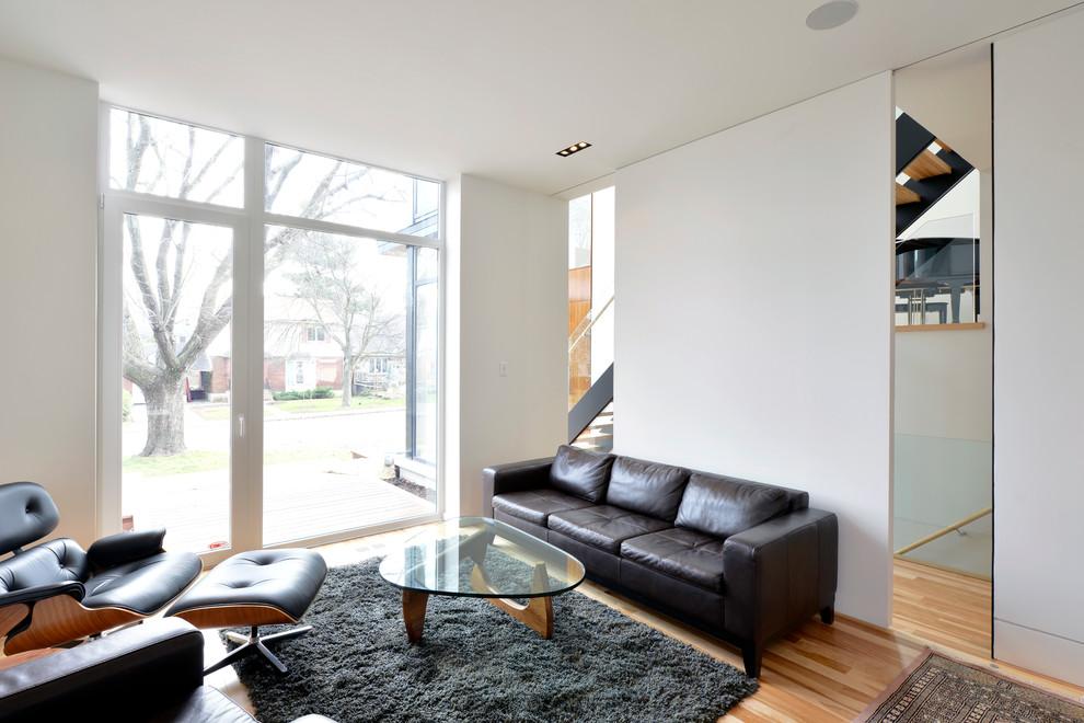Trendy medium tone wood floor living room photo in Ottawa with white walls
