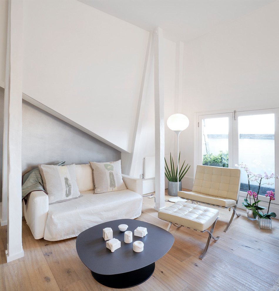 Example of a danish formal light wood floor living room design in London with white walls, no fireplace and no tv