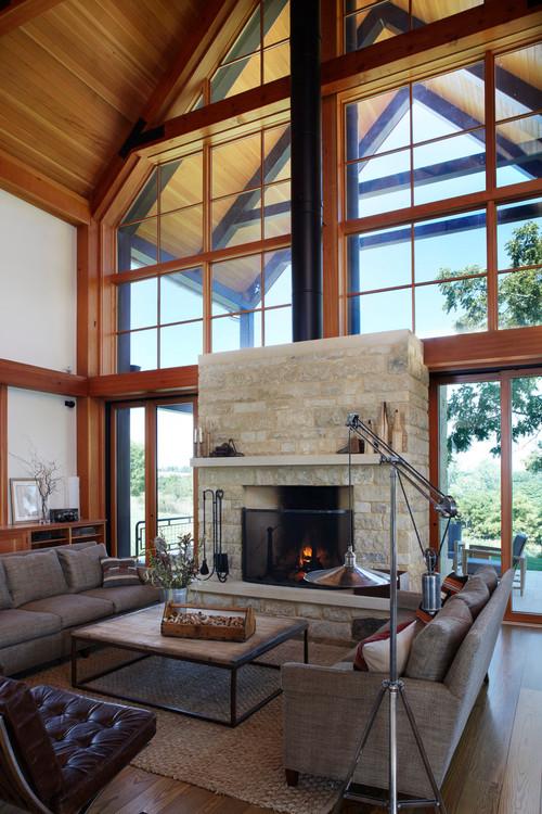 Интерьер с камином в деревянном загородном доме с большим окном под крышей