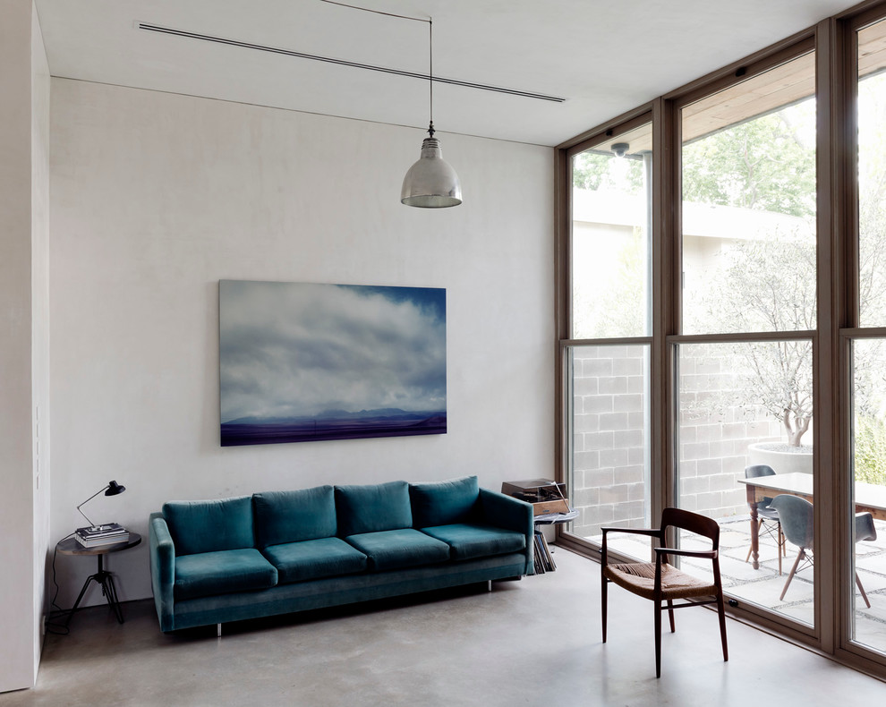 Mid-sized trendy enclosed concrete floor living room photo in Other with white walls