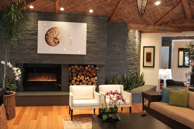 Modern stacked stone veneer dark fireplace.