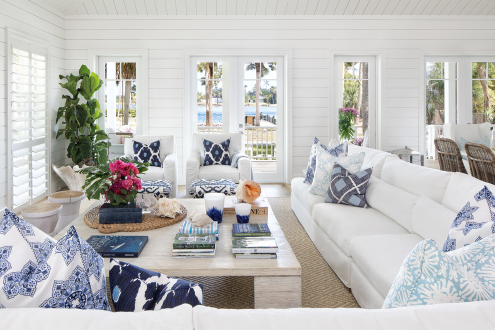 Example of a beach style medium tone wood floor and brown floor living room design in Miami with white walls